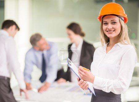 Photo pour Joyeux architecte féminin en casque orange debout au bureau avec l'équipe sur fond . - image libre de droit