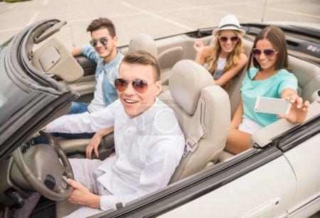 Photo pour Groupe d'amis heureux assis dans le cabriolet. Belles filles prenant un selfie sur les sièges arrière . - image libre de droit