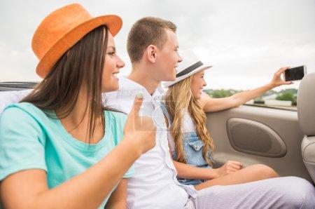 Photo pour Trois beaux amis prenant selfie tout en étant assis dans le cabriolet sur les sièges arrière. Vue latérale . - image libre de droit