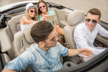 Photo pour Groupe d'amis heureux assis dans le cabriolet. Belles filles prenant un selfi sur les sièges arrière . - image libre de droit