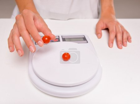 Close-up hands of young woman weighs a tomatoes. C...