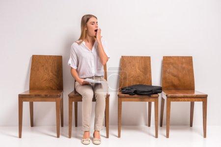 Photo pour Portrait d'une jeune et belle femme en attente d'un entretien d'embauche, assise dans le couloir, sur fond gris. Tournage studio - image libre de droit
