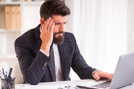 Foto de Dolor de cabeza. Retrato de un hombre de negocios con barba mientras trabajaba en su oficina, sosteniendo la cabeza - Imagen libre de derechos