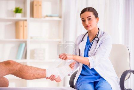 Foto de Pierna de la lesión. Hombre joven con la pierna lesionada. Médico joven ayuda a la paciente - Imagen libre de derechos