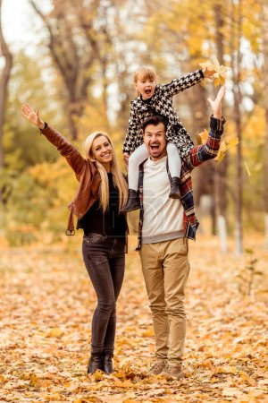 Photo for Young happy family while walking in the autumn park. - Royalty Free Image