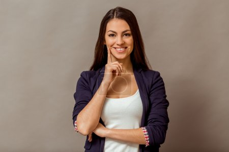 Photo for Portrait of young smiling female standing with folded hands, on a gray background - Royalty Free Image