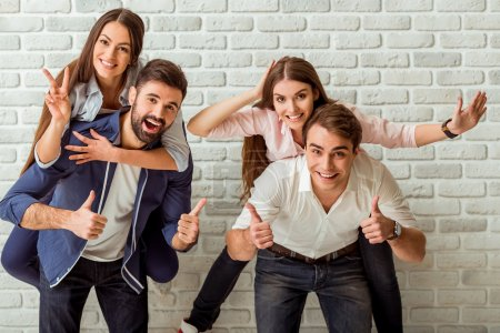 Photo pour Group of happy friends having fun. Men giving a piggyback ride to the girls, smile, look at camera, gesticulating with his hands, against the backdrop of a brick wall - image libre de droit