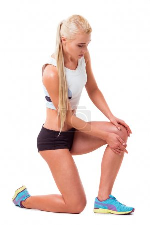 Photo for Beautiful blonde sportswoman kneeling and touching her injured knee, isolated on white background - Royalty Free Image