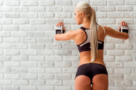 Photo pour Vue arrière de la belle sportive blonde en gants de sport, posant les mains sur le mur, regardant ailleurs, debout contre un mur de briques blanches - image libre de droit
