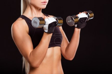 Photo for Beautiful sportswoman in sports gloves posing with dumbbells, isolated on black background, close-up - Royalty Free Image