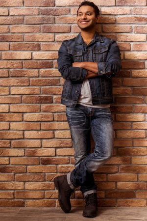 Photo for Young handsome Afro-American man in jeans jacket and jeans looking away and smiling while standing cross-armed against brick wall - Royalty Free Image