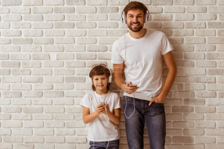 Photo for Handsome young father and his cute little son using smart phones, listening to music, looking in camera and smiling. Both in white t-shirts and jeans, standing against white brick wall. - Royalty Free Image