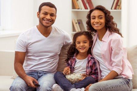 Photo pour Jolie petite fille afro-américaine et ses beaux jeunes parents étreignant, regardant la caméra et souriant tout en étant assis sur un canapé dans la chambre. Père tenant une télécommande, fille tenant un bol avec du pop-corn . - image libre de droit