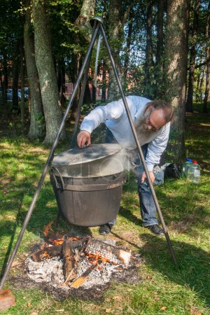 Skilful cook prepares soup over the fire