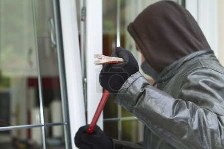 Burglar breaking in a house