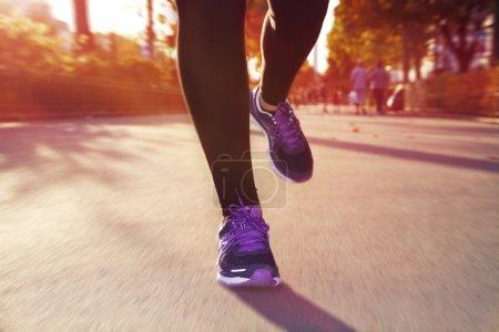 Photo pour Fitness Girl courir au coucher du soleil dans le centre-ville - image libre de droit