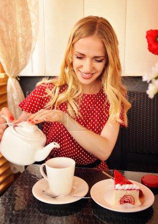 Photo pour Femme blonde versant la tasse de thé et souriant. Tourné dans le café - image libre de droit