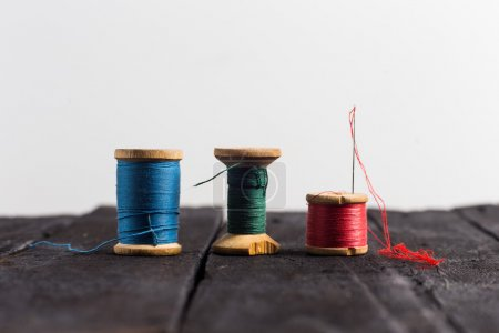 Thread with a needle. Three: green, red and blue t...