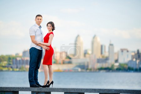 Happy young couple embraces against the city