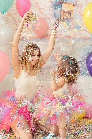 Photo pour Concept de fête des mères. femme heureuse et jeune fille célébrer anniversaire plaing confettis . - image libre de droit