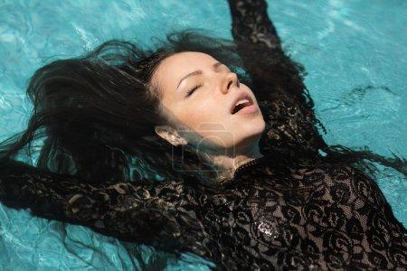 Photo pour Portrait de la belle femme en robe noire flottant en eau bleue - image libre de droit