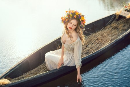 Fantasy art photo of a beautiful lady lying in boat