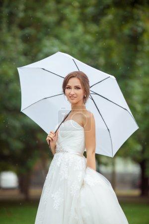 Photo pour Belle mariée dans le parc le jour de pluie avec parapluie blanc à l'extérieur - image libre de droit