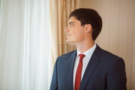 Photo pour Magnifique marié souriant. Bel homme dans une suite avec une boutonnière debout contre une fenêtre à l'intérieur - image libre de droit