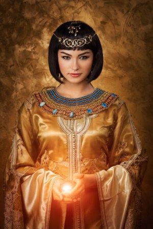 Photo pour Photo de la femme magnifique avec le maquillage de Cleopatra retenant la bille magique d'éclairage - image libre de droit