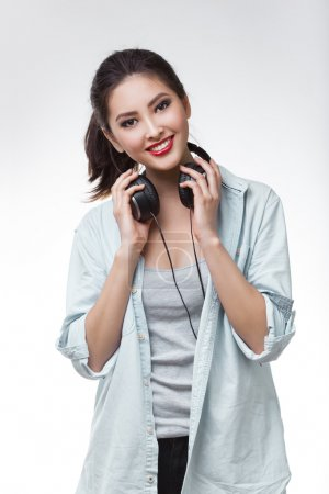 Photo for Music. Woman holding big earphones headphones listening to music on mp3 player. Playful happy smiling young mixed race Asian Caucasian woman isolated on white background. - Royalty Free Image