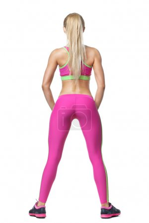 Rear view shot of healthy young woman in sportswear. Full length muscular female model standing against isolated white background