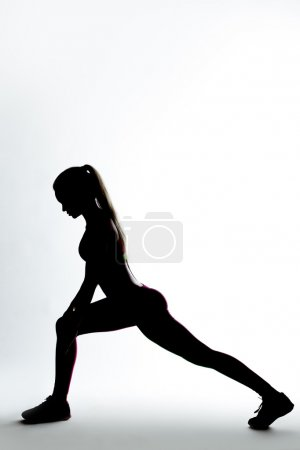 Fitness woman silhouette doing stretching exercise.
