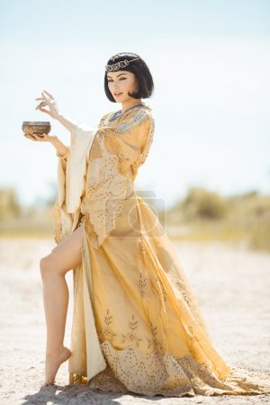 Photo pour Woman pours potion, poisons water. Fashion Stylish Beauty Portrait Holding and Drinking Cup. Girl standing in golden dress outdoors in desert. Hot sunny weather - image libre de droit
