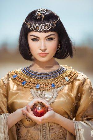 Photo pour Photo de la femme magnifique avec le renivellement de Cléopâtre, portrait de plan rapproché de la belle femelle avec l'agaist élégant de coupe de cheveux, jeune dame utilisant le collier d'or à la mode et retenant la boule de magik extérieure, beauté - image libre de droit