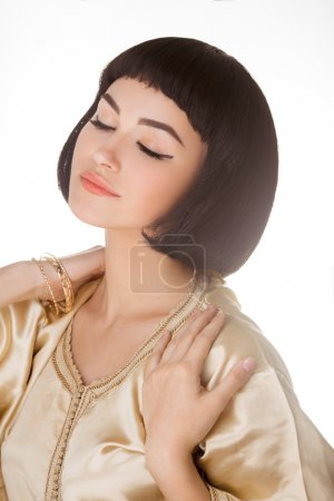 Sensual girl with Cleopatras make-up and haircut posing in studio