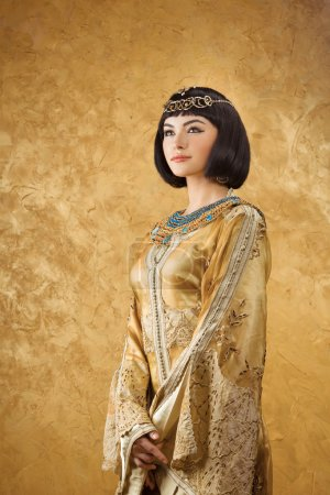 Beautiful woman like Egyptian Queen Cleopatra on golden background