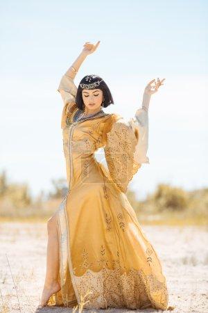 Photo pour Mode beauté élégante femme avec coupe courte noir et maquillage professionnel de Cléopâtre. Jeune fille debout en pleine longueur en robe dorée à l'extérieur dans le désert - image libre de droit