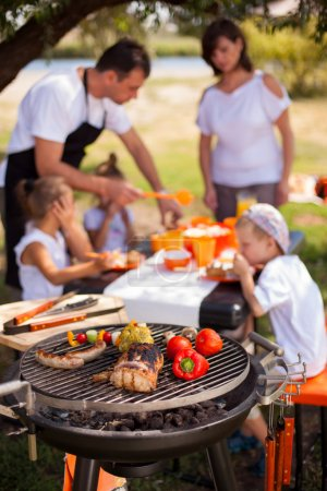 Photo for Family having a barbecue in the garden - focus on grill in the foreground - Royalty Free Image