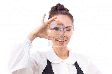 Photo pour Woman looking through a magnifying glass.This photo has been produced with these professionals : make-up artist, hair dresser and stylist. A professional retoucher gave it the final magic touch - image libre de droit