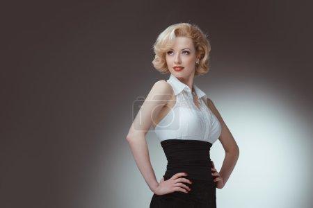Photo pour Pin-up girl, style 50. Prise de vue en studio d'une jeune et belle femme portant une blouse blanche et un essayage noir, en studio. Maquillage professionnel et coiffure - image libre de droit