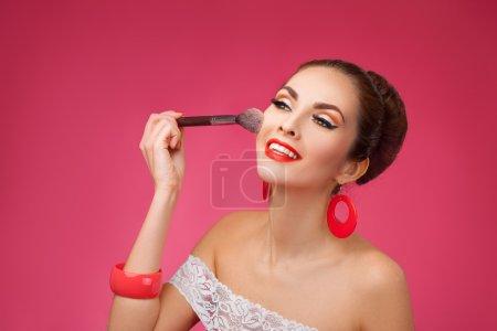 Photo pour Beauté fille avec pinceau de maquillage. Maquillage Naturel pour Brunette Femme. Belle Visage. Relooking. Une peau parfaite. Style rétro Pin-Up - image libre de droit