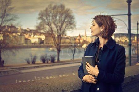 Photo pour Femme allant se promener dans la rue tenant un livre - image libre de droit