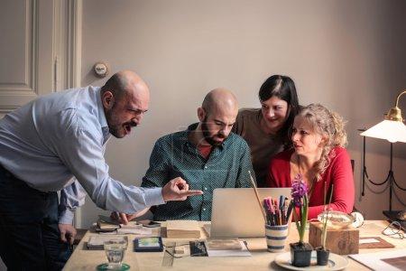 Photo pour Groupe de personnes utilisant un ordinateur et un homme en colère leur criant dessus - image libre de droit