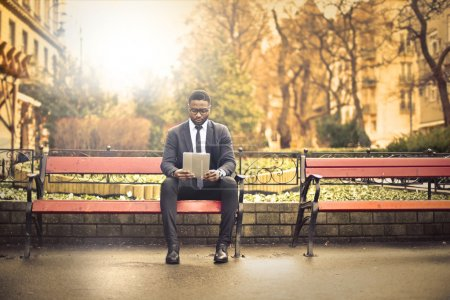 Photo for Man sitting on a bench reading with a tablet - Royalty Free Image