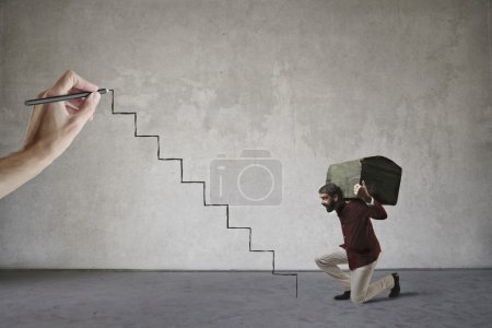Photo for Man climbing stairs carrying a heavy chest - Royalty Free Image