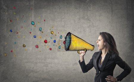 Photo pour Femme d'affaires criant à travers un haut-parleur - image libre de droit