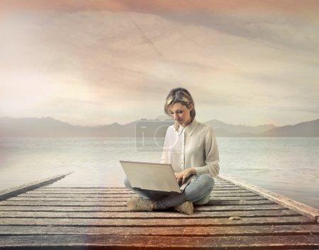 Photo pour Femme travaillant avec un ordinateur au bord de la mer - image libre de droit
