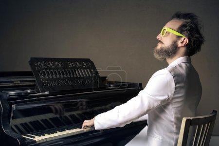 Photo pour Homme avec costume blanc et lunettes de soleil jaunes jouant du piano - image libre de droit