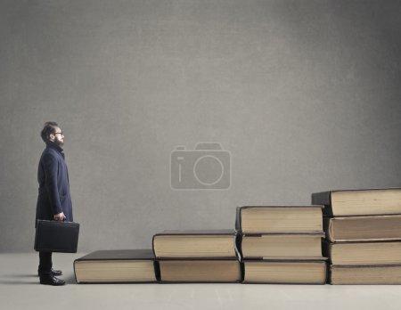 Photo pour Homme d'affaires montant des escaliers faits de livres - image libre de droit