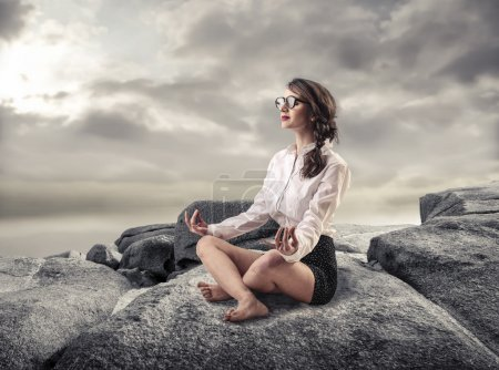 Photo for A young businesswoman is sitting on the top of a rock while meditatig - Royalty Free Image